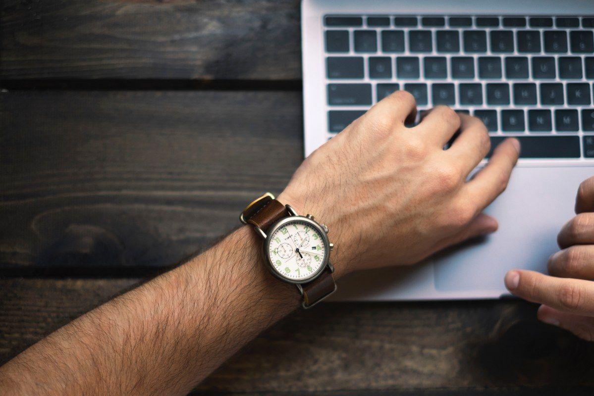 Een man met een horloge om zijn pols achter de laptop voor digitaal factureren