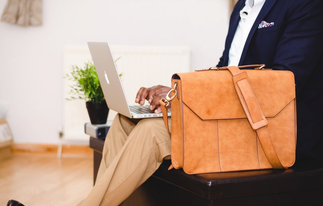A man in a suit with a brow suitcase behind his laptop starting with e-invoicing